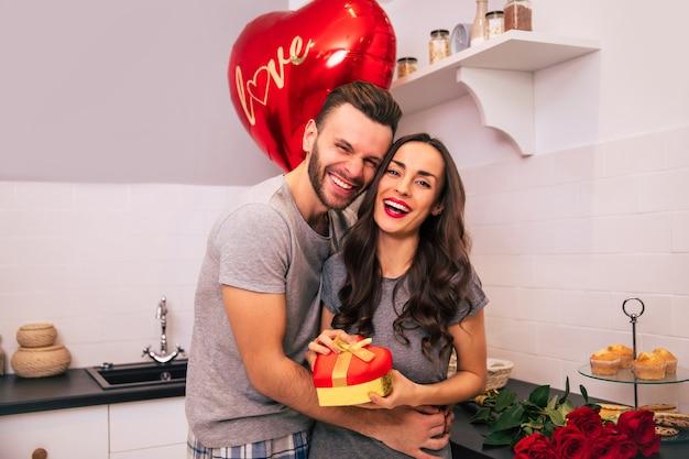매력적인 남자와 가정복을 입은 잘 생긴 여자가 발렌타인 데이에 서로 선물을 주고받으며 부엌에 서서 웃고 있습니다.