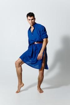 完全な成長の明るい背景に青いドレスを着た魅力的な男は彼の足を持ち上げた