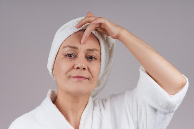 魅力的な成熟した女性が彼女の額に触れています。高齢者のしわの問題。灰色の壁に隔離します。灰色の壁に隔離します。