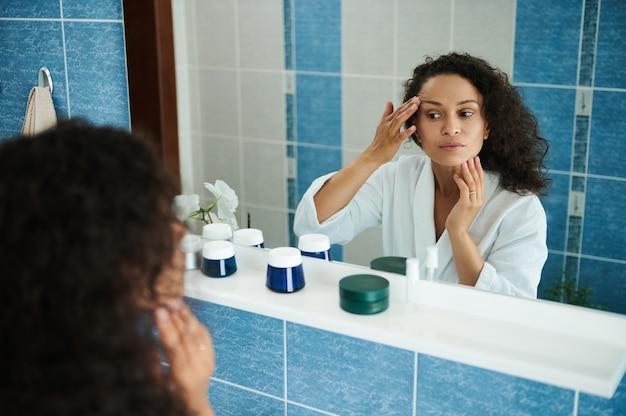 매력적인 중년 아프리카계 미국인 여성이 욕실 거울에 비친 자신의 얼굴과 눈꺼풀을 검사합니다. 스킨 케어 개념
