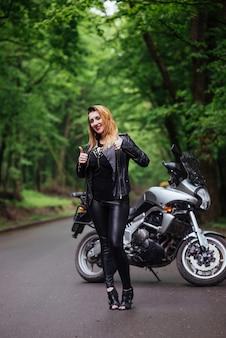 Привлекательная сексуальная девушка, одетая в кожу, позирует возле спортивного мотоцикла на улице