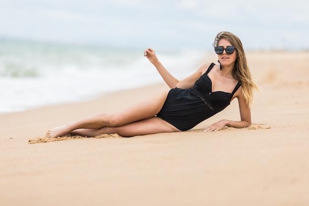 Привлекательная сексуальная женщина в купальнике, лежа на пляже