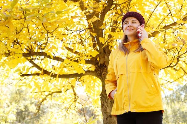 魅力的な笑顔の女性が散歩の秋に電話で話します。テキスト用の空き容量