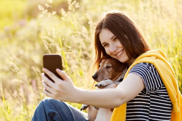 Привлекательная девушка-подросток фотографирует себя и свою собаку с помощью камеры мобильного телефона.