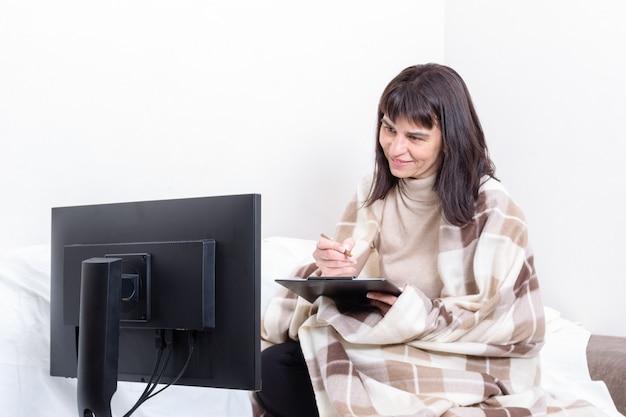 Привлекательная женщина, накрытая одеялом, держит в руках блокнот и внимательно смотрит на монитор компьютера дома