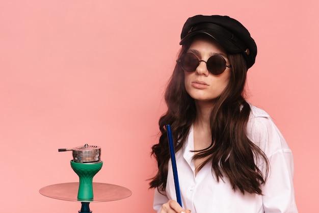모자와 안경을 쓴 매력적인 여성은 물담배, 시샤를 피우고 흡연을 즐깁니다. 핑크 단색 배경입니다.