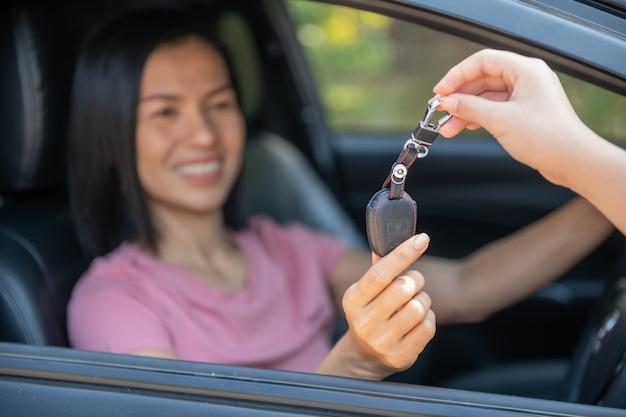 車の中で魅力的な女性が車の鍵を受け取ります。自動車のレンタルまたは購入 – コンセプト。カーディーラーで顧客と仕事をしているプロの販売員。新しい車の所有者に鍵を渡します。