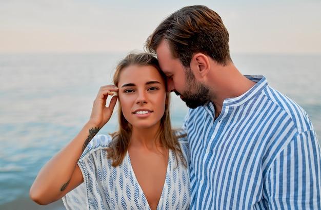 Привлекательная женщина в платье и красивый бородатый мужчина в полосатой рубашке романтически проводят время на берегу моря. влюбленная пара в отпуске.