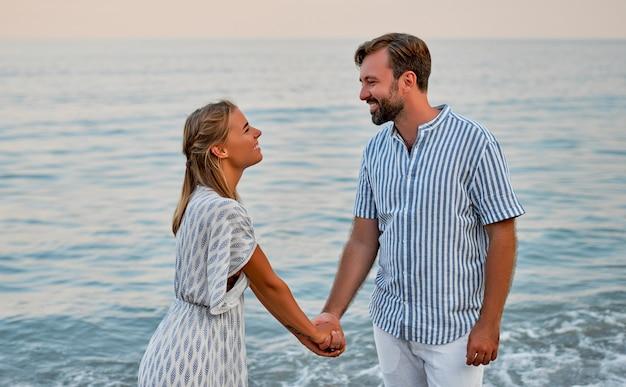 Привлекательная женщина в платье и красивый бородатый мужчина в полосатой рубашке держатся за руки и романтически проводят время на берегу моря. влюбленная пара в отпуске.