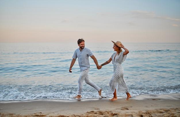 드레스를 입은 매력적인 여자와 스트라이프 셔츠를 입은 잘 생긴 수염 난 남자가 손을 잡고 달리며 해변에서 낭만적으로 시간을 보냅니다. 휴가에 사랑의 부부.
