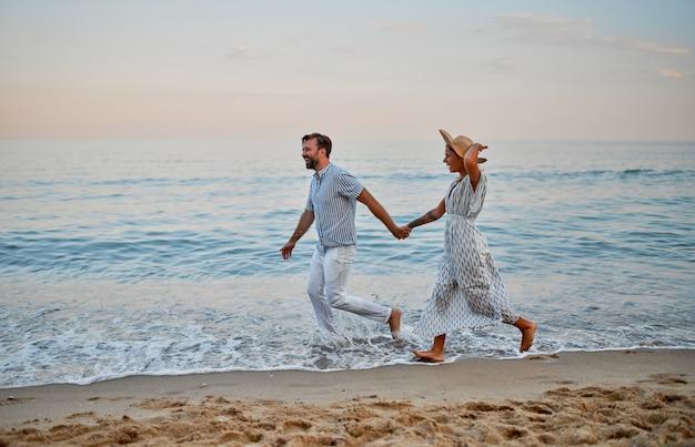 Привлекательная женщина в платье и красивый бородатый мужчина в полосатой рубашке бегают, взявшись за руки, и романтически проводят время на берегу моря. влюбленная пара в отпуске.
