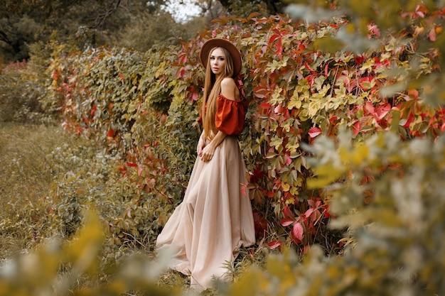 秋の野生の赤ブドウの近くの美しい秋の服を着た魅力的な女性。テキスト用の空き領域。秋のトレンド。ブロガー