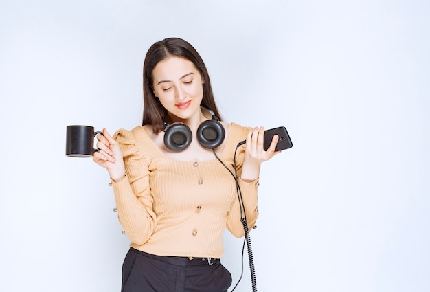 携帯電話とヘッドホンでカップを持っている魅力的な女性モデル。