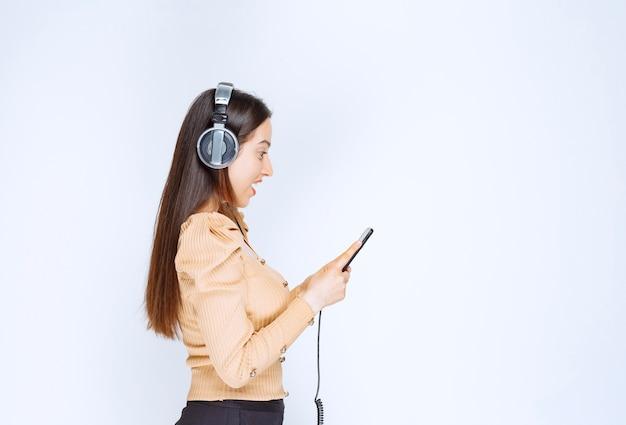 Музыка привлекательной женщины модели слушая в наушниках.