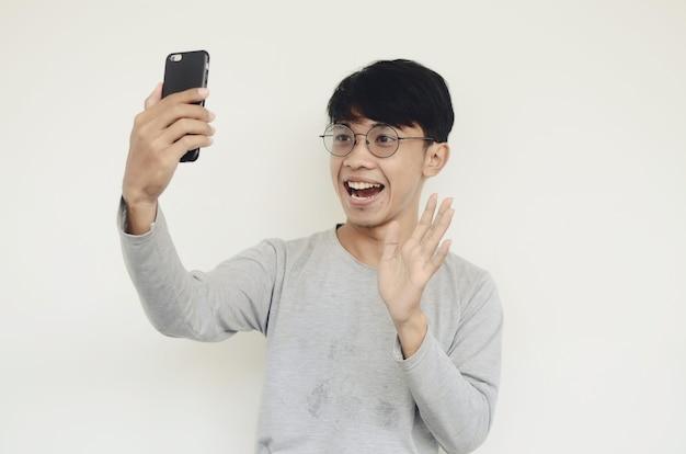 스마트폰을 들고 있는 매력적인 아시아 남자가 화상 통화를 하고 있다