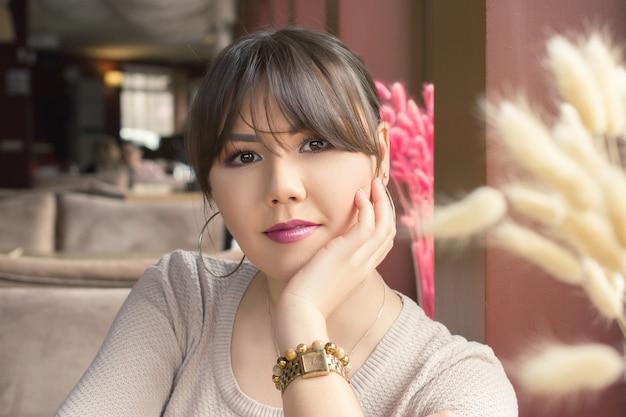 카페 초상화에서 창 옆에 앉아 있는 매력적인 젊은 아시아 여성.