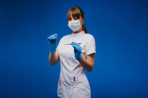 魅力的な若い女性医師がメスを持ってカメラを直接見ています。ヘルスケア、治療、手術の概念。青い背景の上の開業医の肖像画。