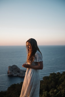 夕方に海を歩いて美しい白いドレスを着た魅力的な若い女性