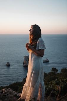저녁에 바다로 걷는 아름다운 하얀 드레스를 입은 매력적인 젊은 여성