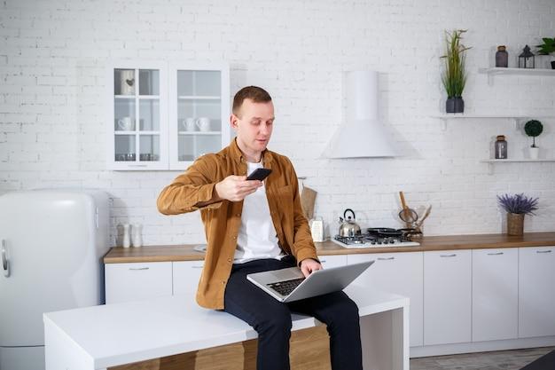Привлекательный молодой человек в повседневной одежде, сидя на кухне с помощью портативного компьютера. работа из дома, удаленный рабочий процесс.