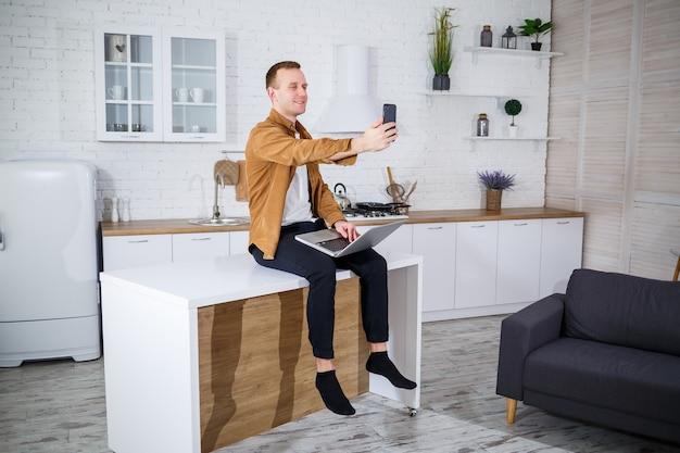 노트북 컴퓨터를 사용하여 부엌에 앉아 캐주얼 옷을 입은 매력적인 젊은 남자. 재택 근무, 원격 워크플로.
