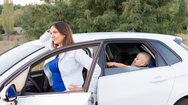 魅力的な若い母親が、駐車中の車のドアに立って、息子を車の後ろに乗せています。