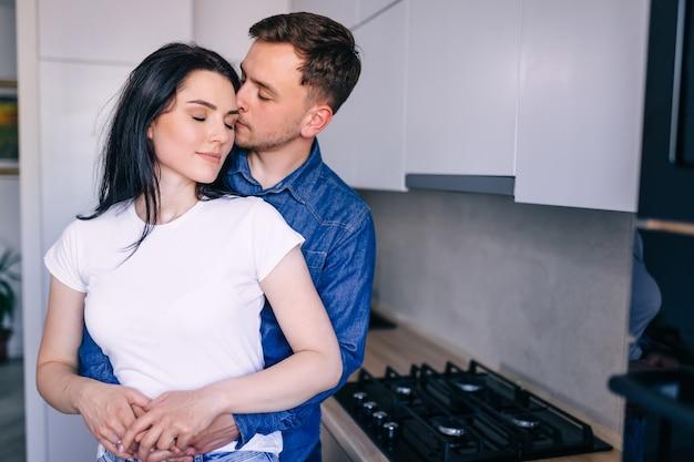 魅力的な若い女性とハンサムな男性は、キッチンに立って一緒に時間を過ごすことを楽しんでいます