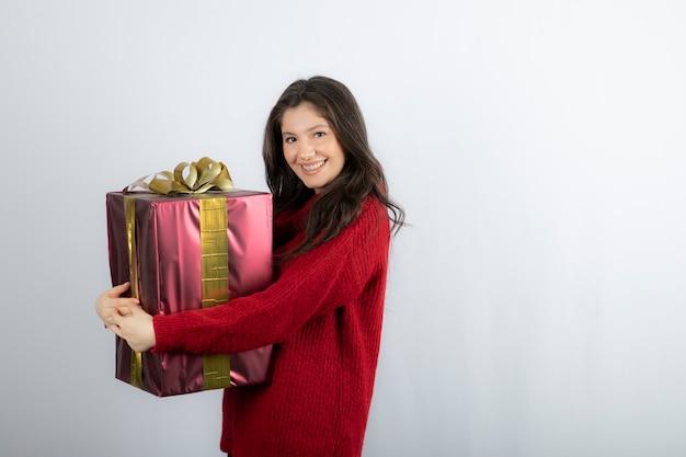 白い壁にクリスマスプレゼントを抱き締める魅力的な若い女性。