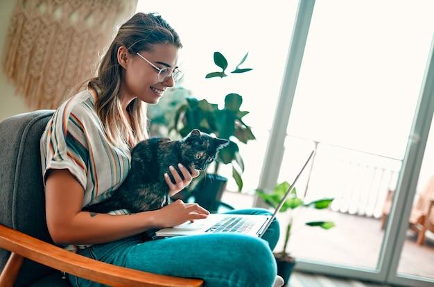 眼鏡をかけた魅力的な若い女性が、自宅の快適な椅子に足を組んで座って、面白いアシスタント猫を足に乗せてラップトップで作業しています。