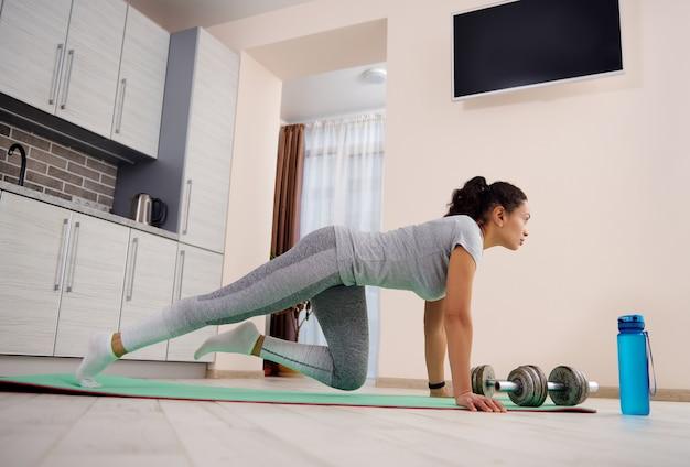 집에서 체력 훈련을 하 고 회색 운동복에 매력적인 젊은 여자. 아령과 전경에 물 한 병