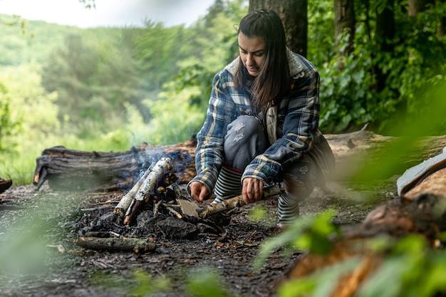 魅力的な若い女性が森の中で暖かく保つために火を起こします