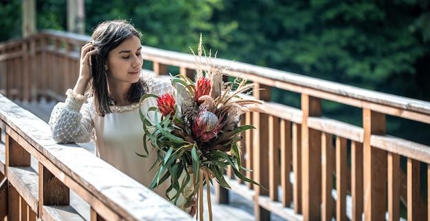 木製の橋の上の魅力的な若い女性は、エキゾチックな花の花束を持って立っています。