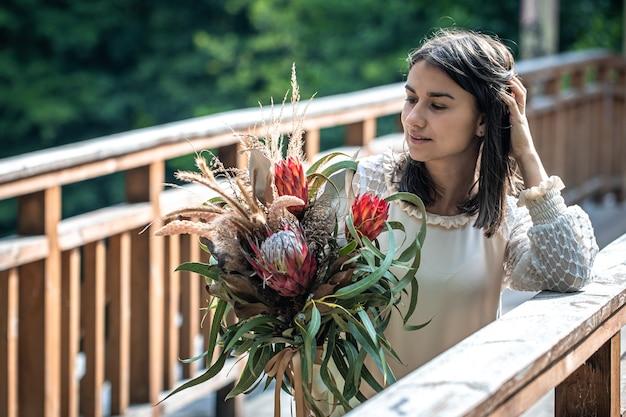 나무 다리에 있는 매력적인 젊은 여성이 이국적인 꽃 꽃다발을 들고 서 있습니다.