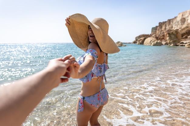 수영복과 큰 모자를 쓰고 해변에 있는 매력적인 젊은 여성이 남자와 손을 잡고 걷습니다.