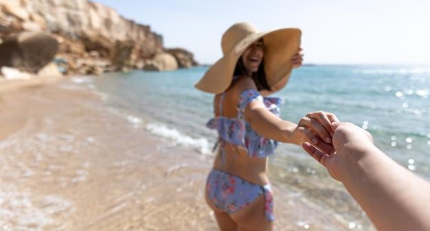 Привлекательная молодая женщина на берегу моря в купальнике и большой шляпе идет за руку с парнем.