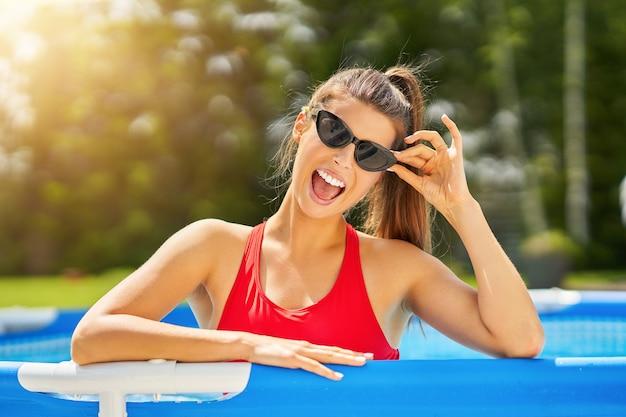 Привлекательная молодая женщина отдыхает в бассейне на заднем дворе