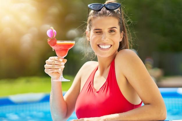 裏庭のプールでリラックスした魅力的な若い女性