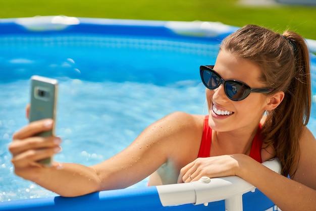 뒷마당에서 수영장에서 편안한 매력적인 젊은 여자