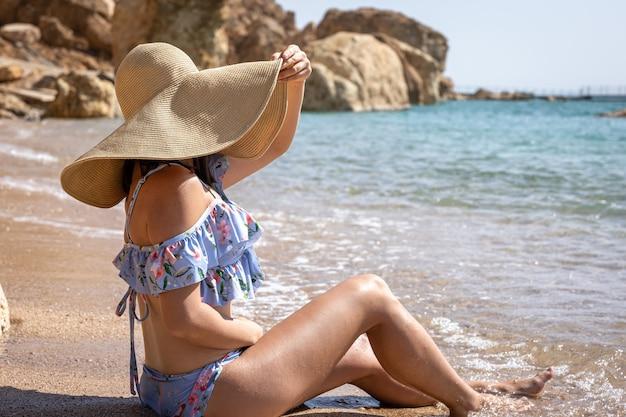魅力的な若い女性が水着と大きな帽子と日光浴で海岸に座っています。