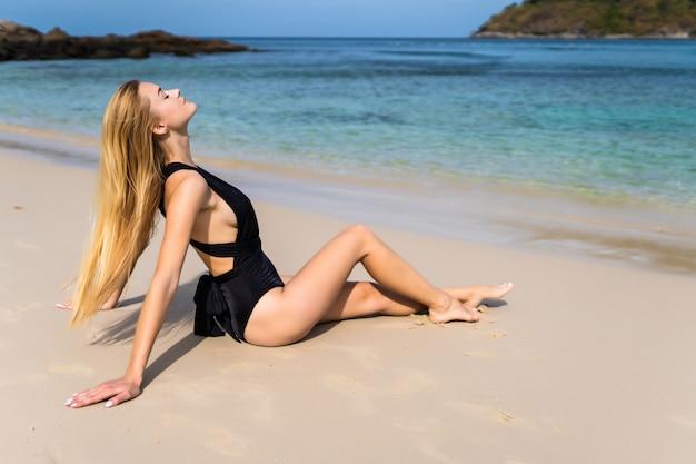 Привлекательная молодая женщина в черном бикини сидит на пляже