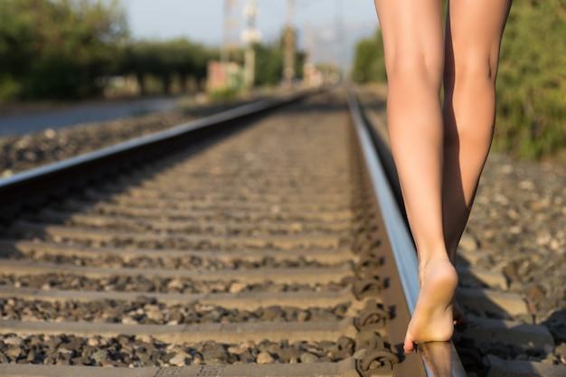 鉄道の近くを歩いている長い茶色の髪の魅力的な若い女性。