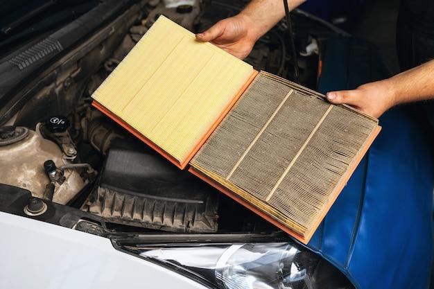 자동차 정비사가 비교를 위해 두 개의 엔진 공기 필터를 보여줍니다. 하나는 오래된 것과 다른 하나는 새 것입니다.