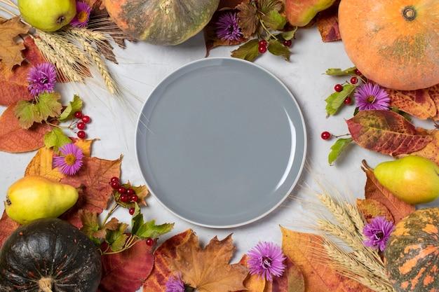 호박, 배, 잎, 꽃, 가막살 나무속, 밀 귀, 텍스트를위한 공간이있는 중앙에 회색 접시로 구성된 가을 수확 프레임. 위에서 봅니다.