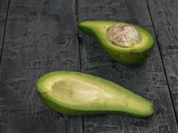 나무 테이블에 반으로 자른 아보카도. 식물성 식품.