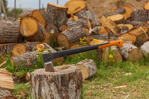 Топор в деревянной балке на фоне кучи деревянных дров Premium Фотографии