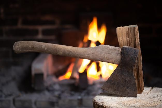 燃える暖炉の近くの木の切り株に斧が刺さった。村の快適さとリラクゼーションの概念。