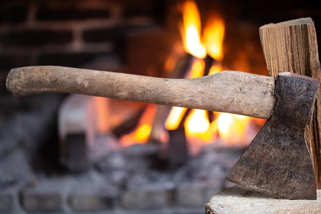 Топор воткнут в деревянный пень возле горящего очага. концепция уюта и отдыха в деревне.