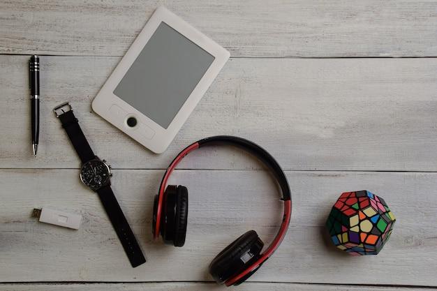 На бежевом деревянном столе лежат электронная книга, наручные часы, кубик рубика, наушники и ручка.