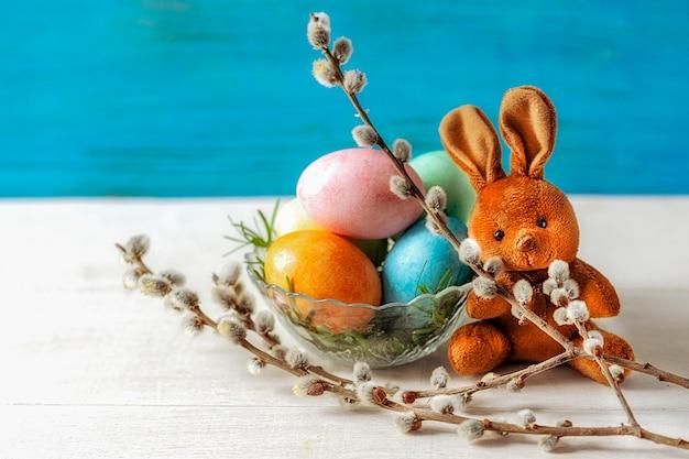 Сидит пасхальный коричневый кролик, перед ним в вазе с зеленой травой пасхальные яйца, веточка вербы. синий фон, выборочный фокус.