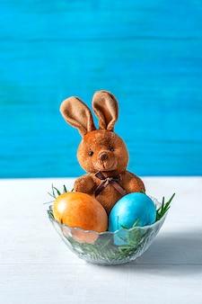 イースターブラウンのウサギのおもちゃが座っており、その前にある緑の草の花瓶にイースターエッグが2つあります。青い背景、セレクティブフォーカス。
